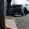 A bouquet of flowers lays on the sidewalk of Glenwood Ave near a car involved in Sunday morning's fatal accident as a TV news photographer films Sunday afternoon March 21, 2010. Item Photo/ Reba M. Saldanha