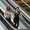 Susan Yee, manager of the Square One Mall in Saugus, with Lauren Sacilotto, a senior at Saugus High, Susan's shadow for the day, riding down the stairs at the Square One Mall.