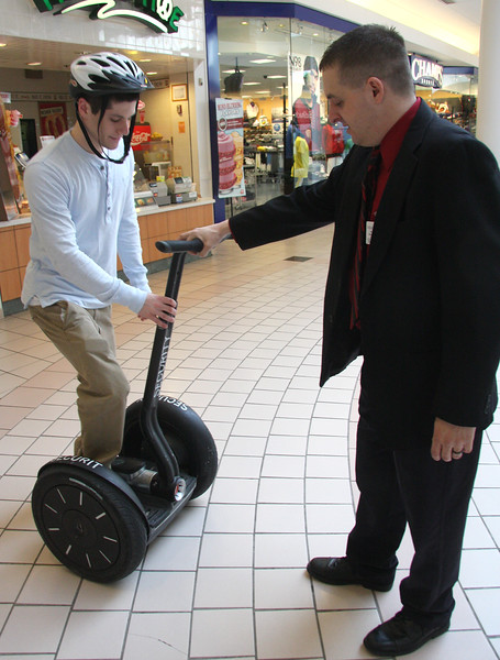 Craig Vezina, head of security at the Square One Mall, instructs Mike Supino, a senior at Saugus High, on how to ride a Segway.