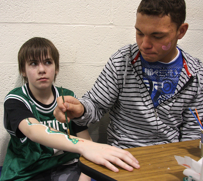 Winter Fest at the Johnson School in Nahant on Saturday. Faces weren't the only thing painted at the face painting table. Cameron Rogers had Lesly Yankelevich paint a snake on his arm.