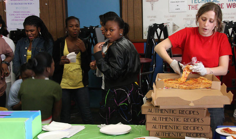 Annual HALT conference held at Lynn Tech. Sara Fox of Girl's Inc cuts pizza for distribution from Effie's Pizza. 15 Lynn restaurants donated pizza to the event.