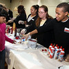 Staff Claude Exama and Danielle Tallent serve ice cream to Kaylee Smith at the Lynn YMCA Family FUn night Monday April 12, 2010. Item Photo/ Reba M. Saldanha