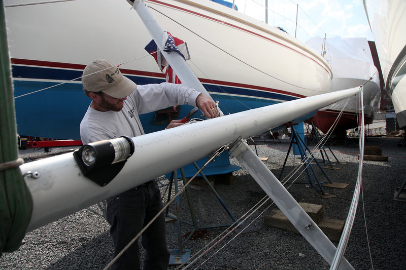 "John Fitchman of North East Rigging company removes the mast for repair from ""Go Figure"", a sailboat in dry dock at the Lynn Yatch Club Thursday April 22, 2010. Item Photo/ Reba M. Saldanha"