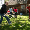 Michelle Shabarek plays with a colonial game called stick and hoop while Alexis Cicco tries her hand walking with stilts at the Saugus Iron Works on Saturday. the new Junior Ranger building is in the background.