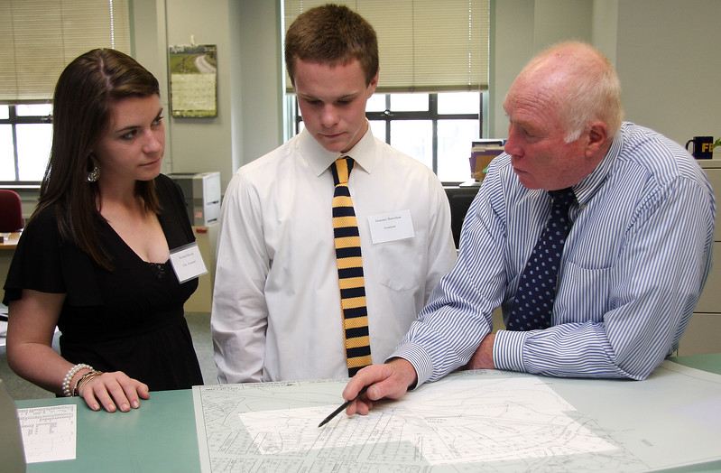 Student Government Day in Lynn. George Brennan, Assessor, shows Kristen Moccia, City Assessor and Dominie Barceleau Assessor, where their houses are located, how much their parents paid for it.