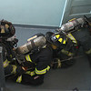 Using masks filled with waxed paper to simulate smoke conditions, four fire fighters--John Kane, Tim Laighton, Matt Patterson, and Mark Andrian-- with a rope as a guide, crawl into a building to rescue a fallen fire fighter.