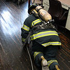 Using wax paper in their masks to simulate smoke, Lynn fire fighter make their into the room containing an unconscious fire fighter.