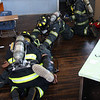 John Kane, Tim Laighton, and Matt Patterson drag the unconscious fire fighter out of the room.