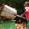 Christine Hernandez fills barrel after barrel at the Henry Avenue cleanup in Lynn on Saturday.