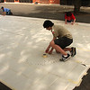 Peter Louvaris and others under his supervision tape down the stencil that he will use to paint a map of the United States in the playground at the Drewicz School in Lynn on Saturday as part of an Eagle Scout project.