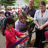 Sarah's mom Katie cuts the ribbon, with a little help from Maria Peguero, at the entrance of 162 Curwin Circle dedicated to Sarah Allyn today. Rob Allyn and Cathy Rowe, Youth Director at the Center.