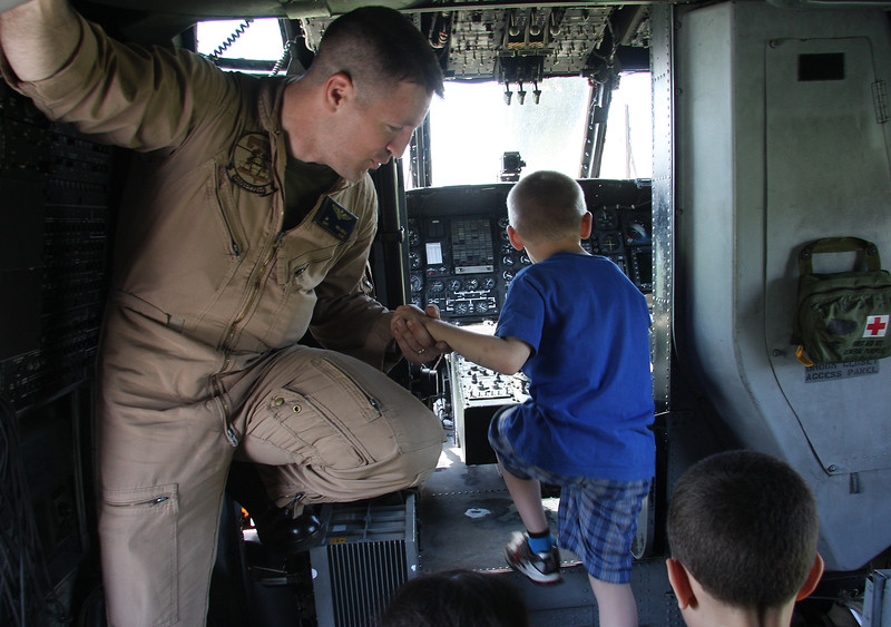 Marine Captain Jeff Hullinger gives John Anderson a hand into the cockpit of the CH-53E Super Stallion helicopter at Lynn English High School today.