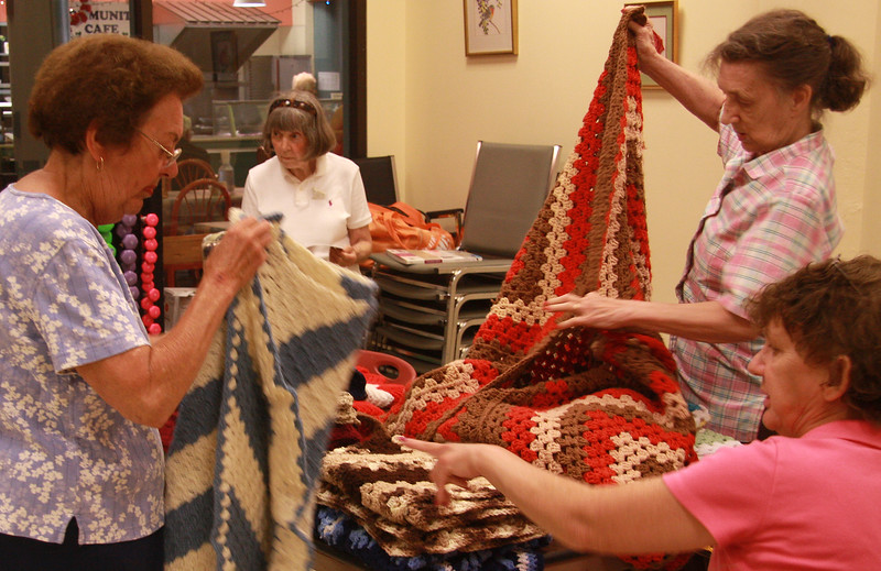 Maureen Beaudet, left, Ellen Coughlan, Hazel Reinholm, and Ethel Forse with some of the quilts they have made.