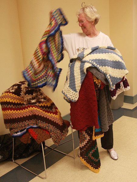 Claire Cahoon with just some of the material created by members of the Knitting and Conversation group at the Lynn Senior Center.