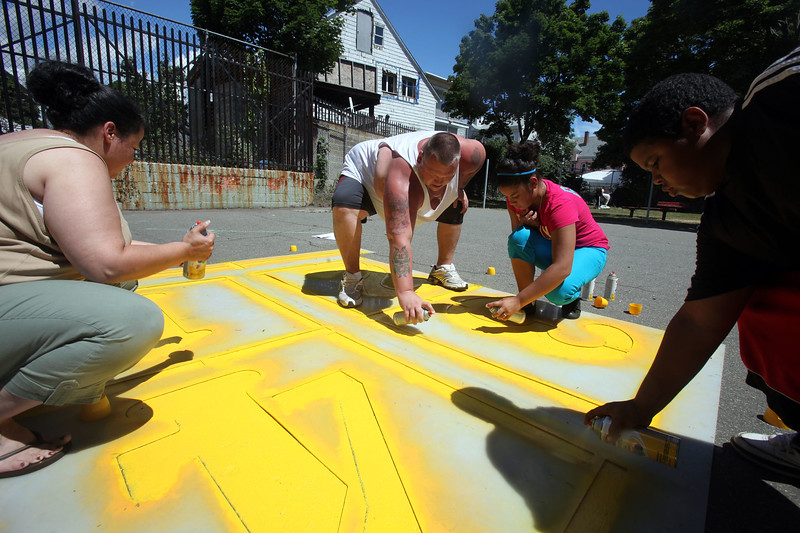 (from left) Amy Robinson, Johnny Fluery, April Cintron and Andre RObinson paint a four square grid at the Williams Ave playground clean up Saturday July 10, 2010. Item Photo/ Reba M. Saldanha