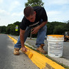 Anthony Howell, a student at Methodist University, paints curbs at Saugus High School as part of his summer job with the Saugus department of public works on Tuesday July 13, 2010. Item Photo/ Reba M. Saldanha