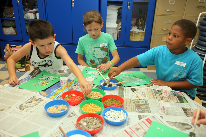 From left, Tyler Wilson, Casyn Scarpaci, and Tre Sanders  make a seed mosaics at the Saugus library's 'go green' day Thursday July 15, 2010. Reba M. Saldanha