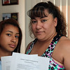 Elizabeth Muriel poses with her daughter Waleska, 13, and correspondence from party planner Donna Garcia in her Lynn home Thursday July 15, 2010. Reba M. Saldanha