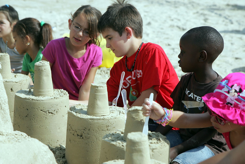 Brooke and Mason White and Amiyr Ahmad, right,  learn how to make a sandcastle at Revere Beach's annual sand sculpture competition Saturday July 17, 2010. Item Photo/ reba M. Saldanha