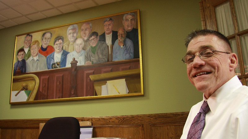 Mike Mahoney in his office in Lynn. Behind him is a painting containing his family and friends.