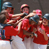 Phil Garraud is greeted by his team mates after he hit a home run for East Lynn. City Series.