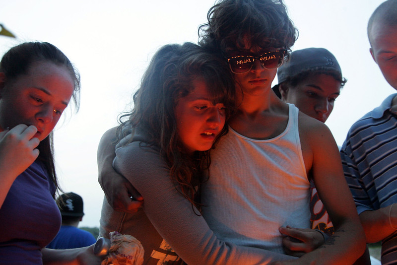 """Mourners (from left) Melissa Basanisi, Brianna Doucette, and Marc Grogan look at candles that spell """"Salim"""" during a memorial for drowning victim Salim Fort near where he drowned Tuesday in Breed's Pond Wednesday July 28, 2010. Item Photo/ Reba M. Saldanha"""