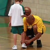 Referee Flynn Manalaysay ties his son Miles's shoe at half time Fecteau Leary School city Basketball