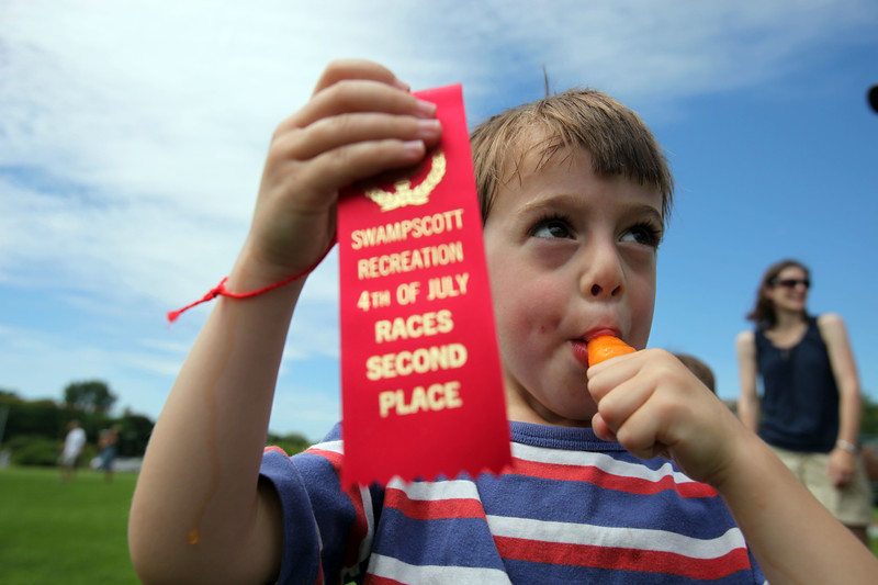 Den Zamansky enjoys a popsile while showing off his second place ribbon during the Swampscott July 4 races at Phillips Park SundayJuly 4, 2010. Item Photo/ Reba M. Saldanha