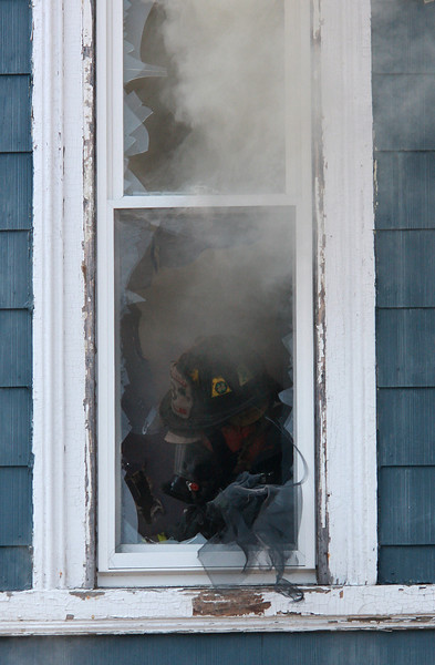 A shot of a Lynn fire fighter battling the fire at 13 Portland Street in Lynn today, taken through the front window.
