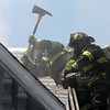 Lynn fire fighters cut a second hole in the roof, this one in the gable in the font of the house to vent the fire  that broke out just after noon at Portland Street in Lynn.