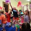 Noah Csank (middle with orange shorts and black shirt) throws his scarf in the air along with others as a break from listening to stories at story time at the Lynn Public Library today.