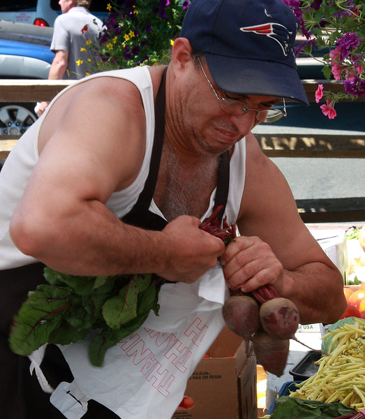 Juan Tejeda prepares produce for a customer at the Farmer's Market in Lynn today.