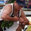 Juan Tejeda prepares produce for a customer at the Farmer's Market in Lynn today.