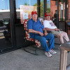 Robert Pacheco, left, and Charlie Vizena beat the heat by sitting in the shade on the porch at GLSS in Lynn.
