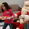 Ixia Andino leaves Santa's lap with a gift, as did every child at the Lynn Housing authority and Neighborhood Development Christmas party held at the Lynn Housing Authority today.