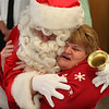 Santa entered the room and either shook hands or hugged everyone, including teachers like Deborah Masone, before getting down to the business of giving out gifts to the students at the Washsington School during the Lynn Housing Authority Neighborhood Development Christmas party held at the Lynn Housing Authority today.