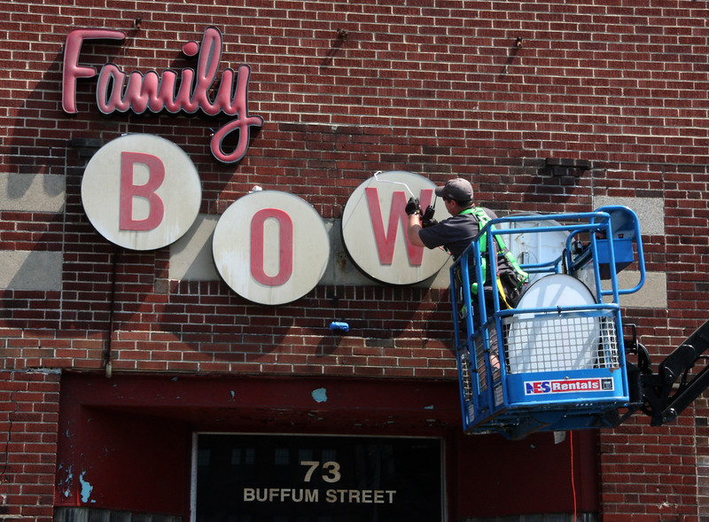 Ray McLaughlin of the electrical department installs a sign on the outside of the Lucy Strike Bowling Alley on Buffum Street in Lynn today in preparation for the Adam Sandler Shoot there later today