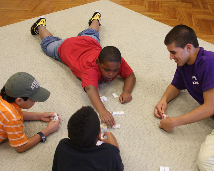 United Way young Lynn leader Neil Whittredge plays dominos with Edwin Ramos, orange shirt, Nicolas Flint, and Jeffery Gordils, red shirt. at the Gregg House today.