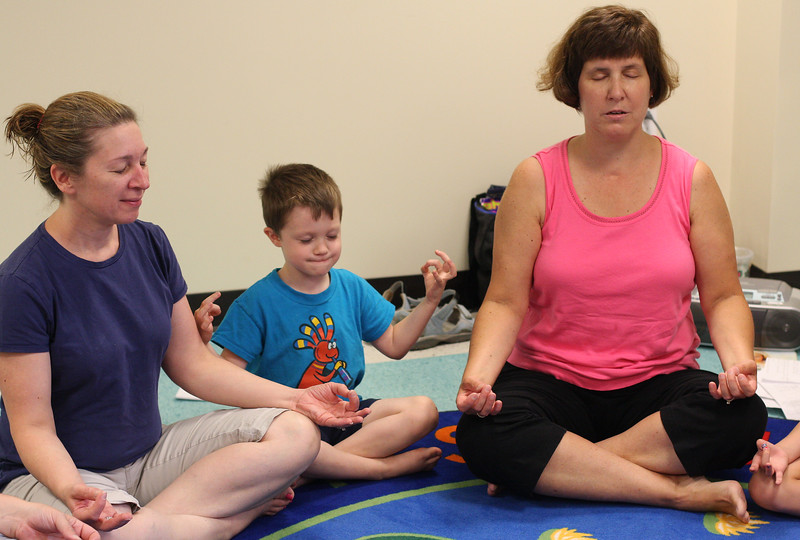 Betsy Reid, right, strikes a relaxing meditative yoga pose with students Denise and Timmy Eagan at today's Yoga with Betsy class, a special child/parent yoga program for children ages 3-5 held at the Peabody Institute Library. The next yoga session is on August 4th at 9:30 am.