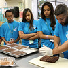 Camp Explorer is many things including cooking. Here Tony Canadas show his class, Dayenny Morel, Elicia Torres Ali Jallow, and Shawn Davis,  how to cut brownies.