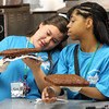 Jelissa Morales, left, and Raymi Ramirez, wait to cut brownies at camp Exploreer at Lynn Tech Annex today.