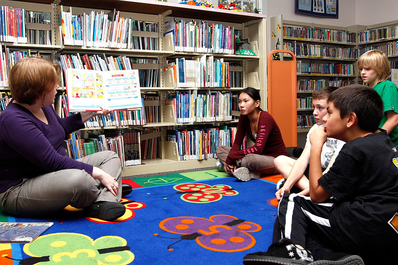 Laura Bruynell, head of youth services, reads a book about ice cream to Laura Pham, age 12, Braden Doyle, age 10, Tyler Walsh, age 11, and Richie Casaletto, age 10, at the Lynnfield Library's middle school Afternoon Discovery group on Thursday, October 13. By Angela Owens.
