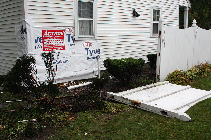 The car traveled through the yard of Phil Torto's neighbor, smashed through this fence and came to rest after puncturing this side of the house.