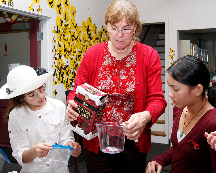 At the Lynnfield Library's middle school Afternoon Discovery group on Thursday, October 13, children's librarian Pam Griswold measures out salt for Abby Zarakovich, age 11, left, and Laura Pham, age 12, right, for their homemade ice cream. By Angela Owens.