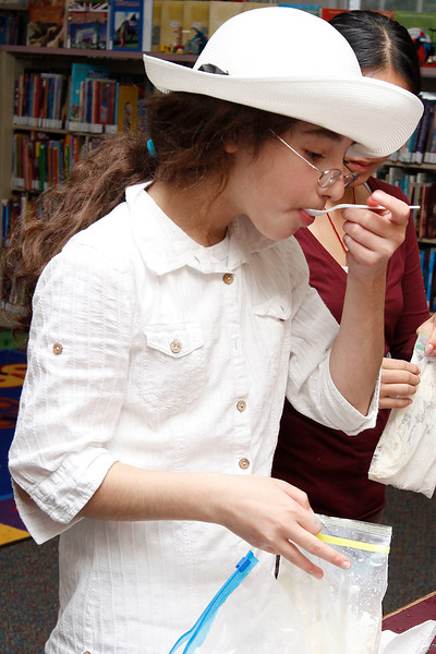 Abby Zarakovich, age 11, tries a spoonful of her homemade vanilla ice cream at the Lynnfield Library's middle school Afternoon Discovery group on Thursday, October 13. By Angela Owens.