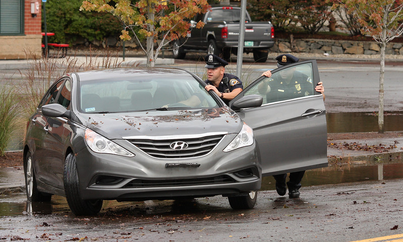 Swampscott Police Officer Kevin Reen, and Sgt. Jay Locke push a disabled car off Paradise Road across from Marshalls Department store just before the road was reopened to traffic this morning.