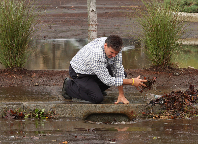 Swampscott DPW director Gino Cresta Jr. cleans out a storm drain on Paradise Road in Vinnin Square this morning.