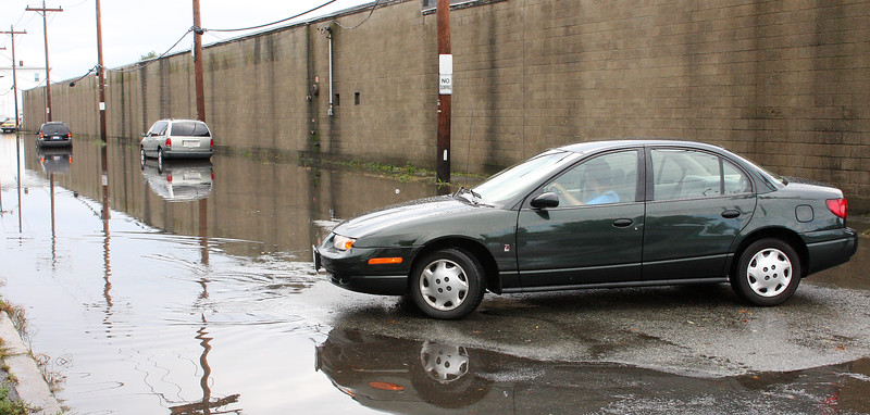 A driver decides to turn around rather than go down Alley Street in Lynn this morning after seeing the water and two disabled vehicles.