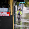 Chris Tighe, Peabody's Emergency Management Director, wades through the water in Peabody Square to look at the flooding in shops on Lowell Street, on Tuesday, October 4. By Angela Owens.