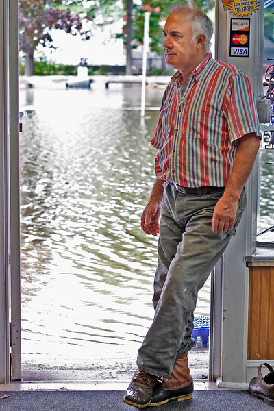 Near Peabody Square on Tuesday, October 4, Demetri Skalkos co-owner of McNamara's Liquors, stands in the doorway to his store, with the flooded Foster St behind him. By Angela Owens.